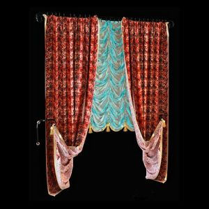 Для пошива классической модели французской шторы была использована двухцветная органза. Яркие акценты цветового оформления ткани привлекают внимание к изящному рисунку драпировки фестонов. Дополняют объёмную штору классические портьеры лаконичного кроя, сшитые из пёстрой ткани со сложным орнаментом. Обрамление боковых полотен золотистой окантовкой, а также одинаковое для всех текстильных элементов декорирование пышными кистями объединяют различные цветом и фактурой элементы.