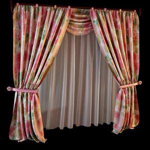 Крупный цветочный мотив длинных шёлковых портьер сочетается по цвету с однотонными атласными подхватами. Белоснежная воздушная гардина простого кроя изящна в простоте линий, она привносит больше света в оформление. Декоративные розетки, выполненные в соответствии с дизайном цветастого рисунка штор, привлекают внимание к мягкому рисунку линий драпировки.