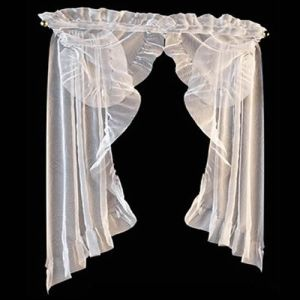 Элементы прозрачного ламбрекена и край штор декорированы оборками с закрытым срезом. Тот же приём используется и в оформлении кулиски, полностью скрывающей штангу карниза. Изящный комплект преобразит небольшое окно, привнесёт особый флёр романтики даже в скромный интерьер. Такой вариант оформления будет уместен в украшении окна спальни, будуара, комнаты девочки.