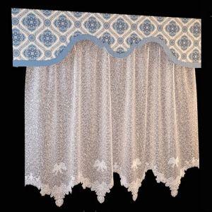 Ламбрекен бандо, выполненный из богато орнаментированной ткани, дополняет белоснежную тюлевую занавеску. Фигурный край ламбрекена подчёркивает однотонный бордюр цвета лазури, соединяя разнофактурный текстиль в единый ансамбль. Важная деталь — длина занавески до подоконника. Такой комплект уместен в оформлении небольших помещений, может использоваться для декора окна кухни или детской.
